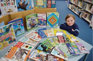 All Saints' College Year 2 student Kaitlyn Martin shows off some of the more than 300 books she won for her school.