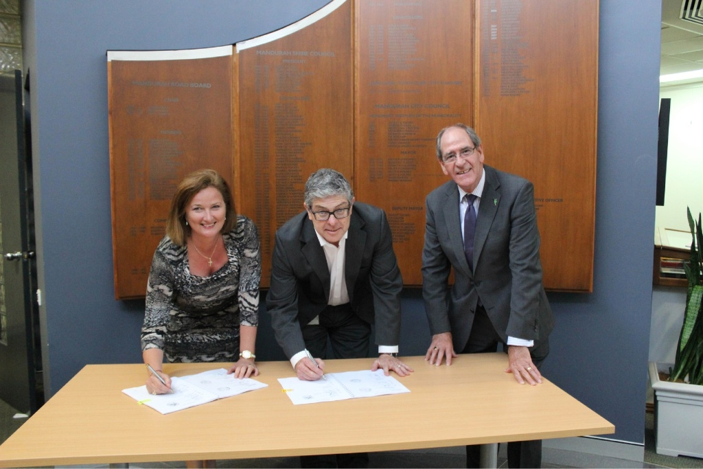 Mandurah Mayor Marina Vergone and city chief executive Mark Newman sign off on the agreement watched by Rivers Regional Council chief executive Alex Sheridan.