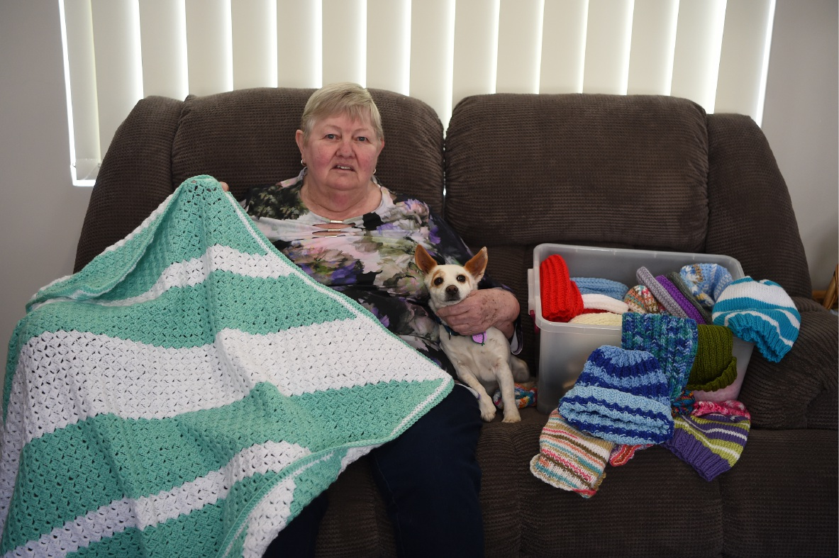 Helen Sinclair knits while her dog Rosey keeps her company.