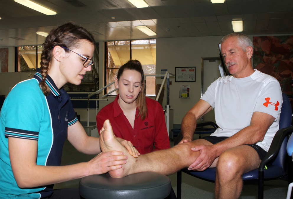 Physio Tuuliki Tulf and occupational therapist Amy Kerman care for Garry Pattinson.  Picture: Robin Kornet        www.communitypix.com.au   d459569