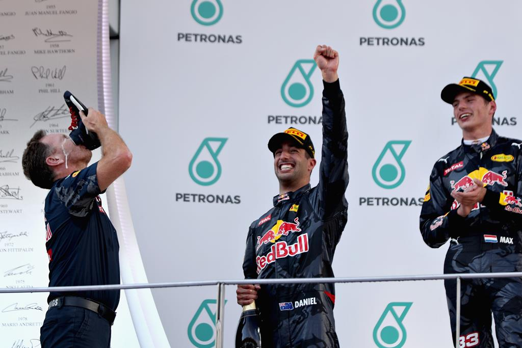 Red Bull Racing Team Principal Christian Horner performs a shoey on stage with Daniel Ricciardo and Max Verstappen .  Picture: Mark Thompson/Getty Images