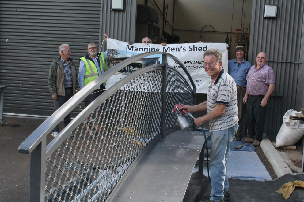 Kingsley Waterhouse gives the new bridge a coat of paint, watched by Manning Men's Shed members Arnold Godfrey, Allan Waugh, Rob Goldfinch, David Winslade, Eric Goddard and Ron Tompkin.