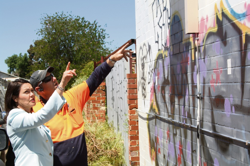 Police Minister Liza Harvey being shown unsightly graffitti by professional graffiti cleaner Troy Reeve.
