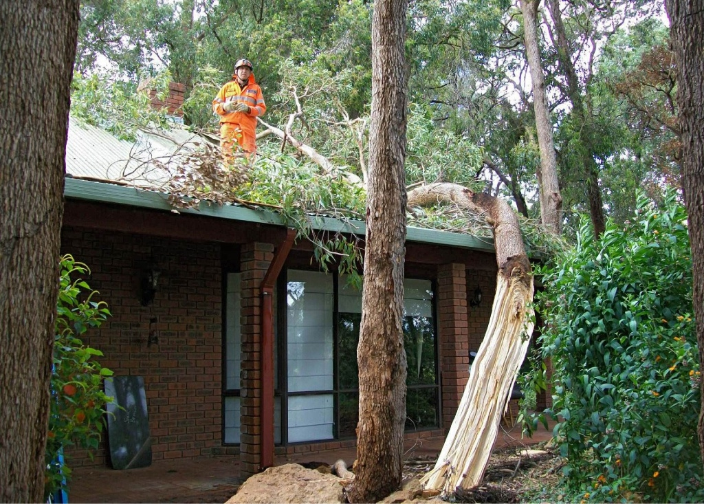 Mundaring SES volunteers help  a resident who home suffered storm damage.