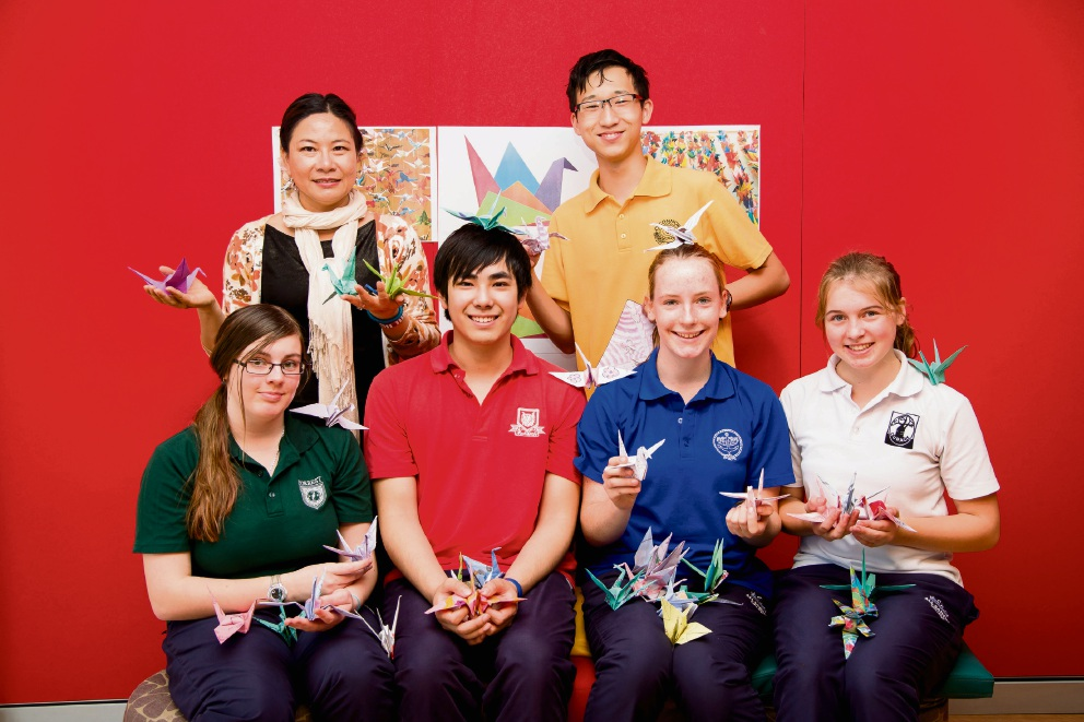College Japanese language specialist Vita Velletri with students and their origami cranes.