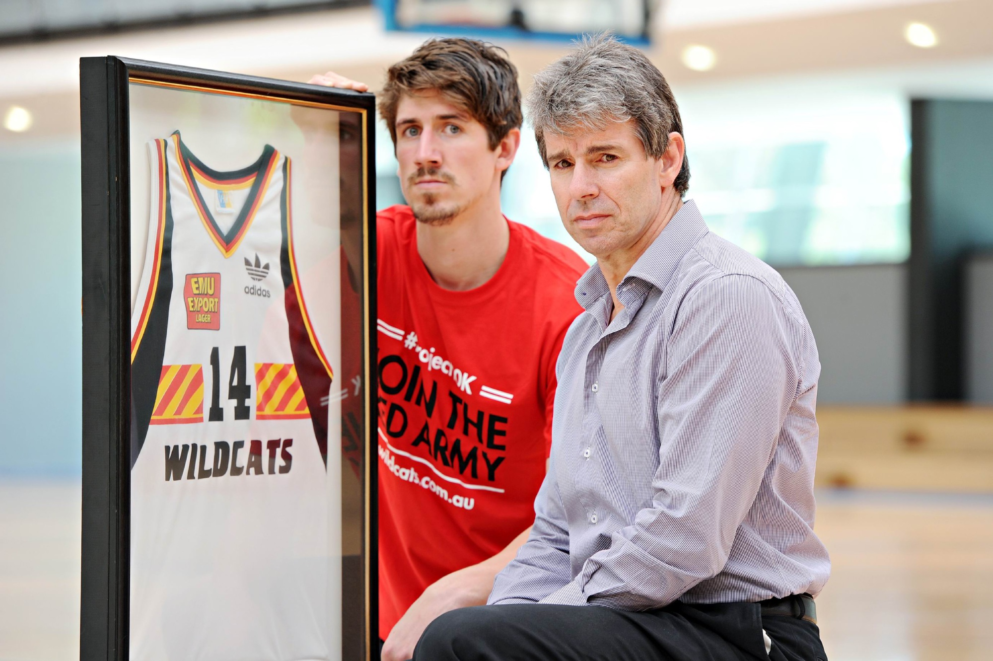 Former Perth Wildcats captain Mike Ellis and current player Greg Hire with Scott Fenton's retired jersey. Picture: Marcus Whisson