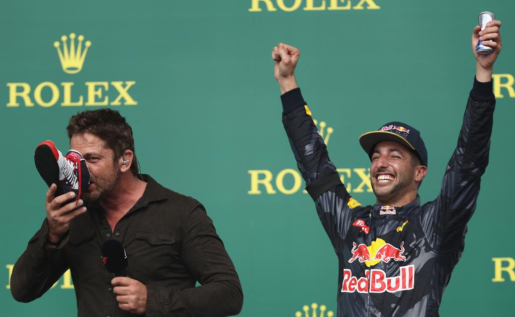 Daniel Ricciardo gets another celebrity to taste the bubbly from his Puma - this time actor Gerard Butler. Picture: Lars Baron/Getty Images