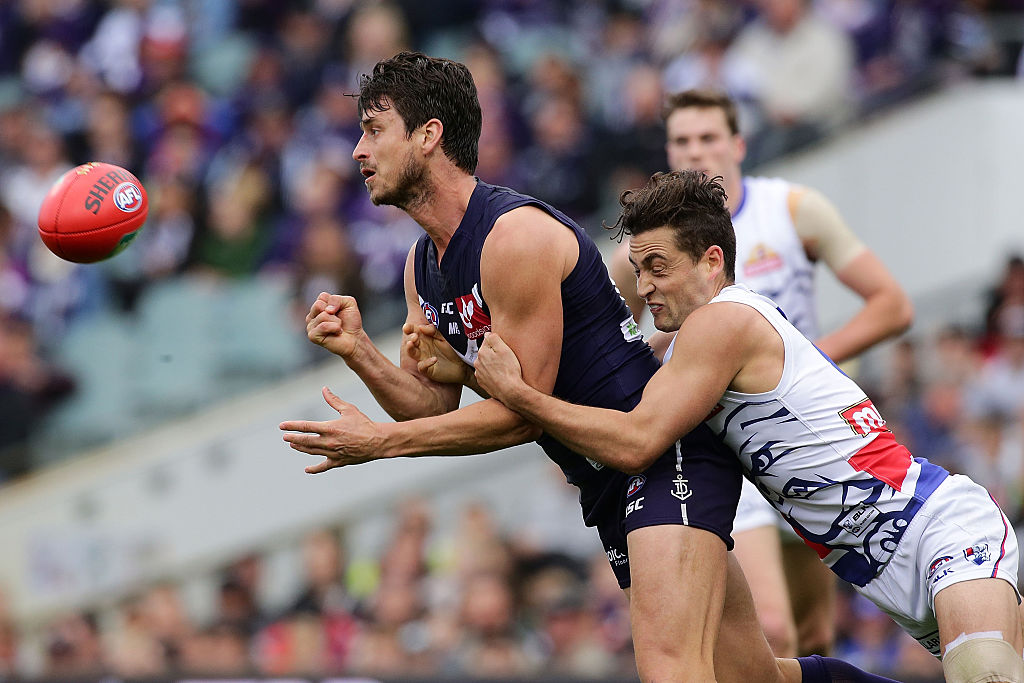 Alex Silvagni handballs under pressure from Luke Dahlhaus of the Bulldogs.  Picture: Will Russell/AFL Media/Getty Images