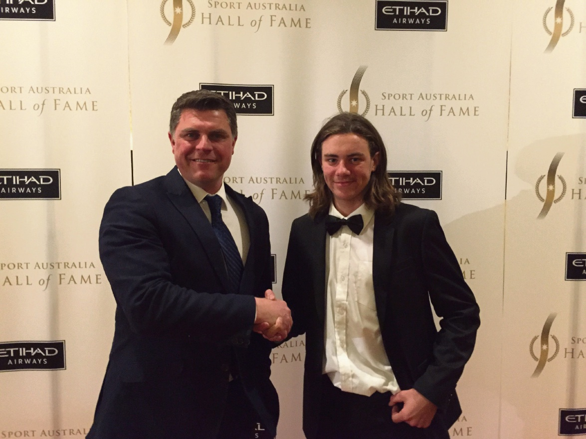 Motorcycling Australia operations and events director Martin Port congratulates Caleb Grothues on winning the scholarship.