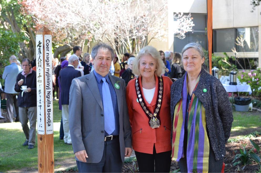 Adrian Glamorgan, Mayor Heather Henderson and Elizabeth Po unveil the peace pole at Rankin Gardens.