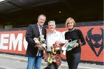 Kicks 4 Kidz director and founder Rod Willet accepts boots from Perth Demons supporter Barry Mather and his wife Dianne.