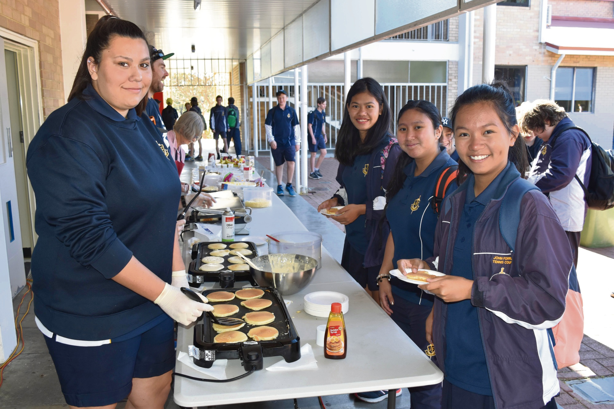 Year 11 student Simone Cronje serves up pikelets to Year 10 students Angela Erika Dela Cruz, Asha De Leon and Christine Sinon.