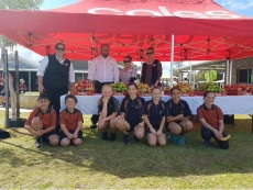 Ashlee Moore with Coles department managers Evan Bester, Kayla Burnett and Camille Childe and students at the Crunch Day fruit stall.