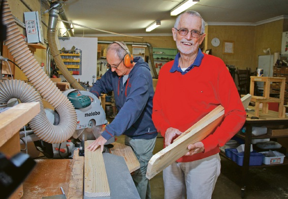 President of Canning Men's Shed Don Buchanan (at right) and Roy Duvall using the new 12 inch Drop Saw purchased with the new funds. Picture: Marie Nirme