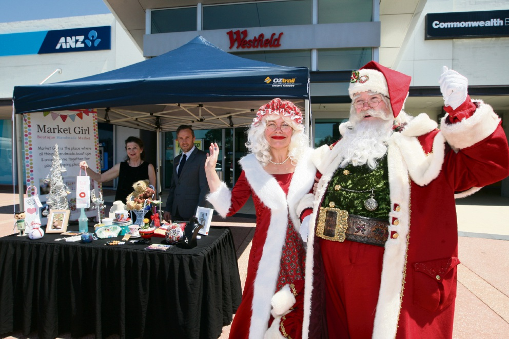 Community Christmas: Stallholder Mandy Ellen, centre manager Scott Greenwood, Mrs Claus and Father Christmas prepare to ring in the Christmas shopping season.  Picture: Bruce Hunt        d461648