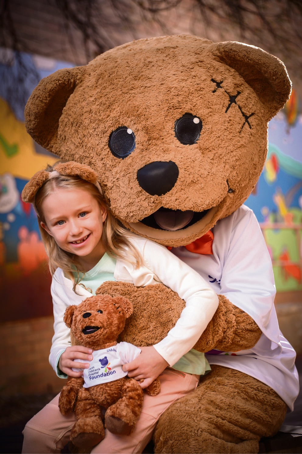 Maya Robertson (8), who suffered second-degree burns on her foot, poses with Stitches the Bear.