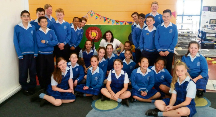 Artist in residence Lauren Tarver and some St Luke's Catholic Primary year 6 students with the artwork.