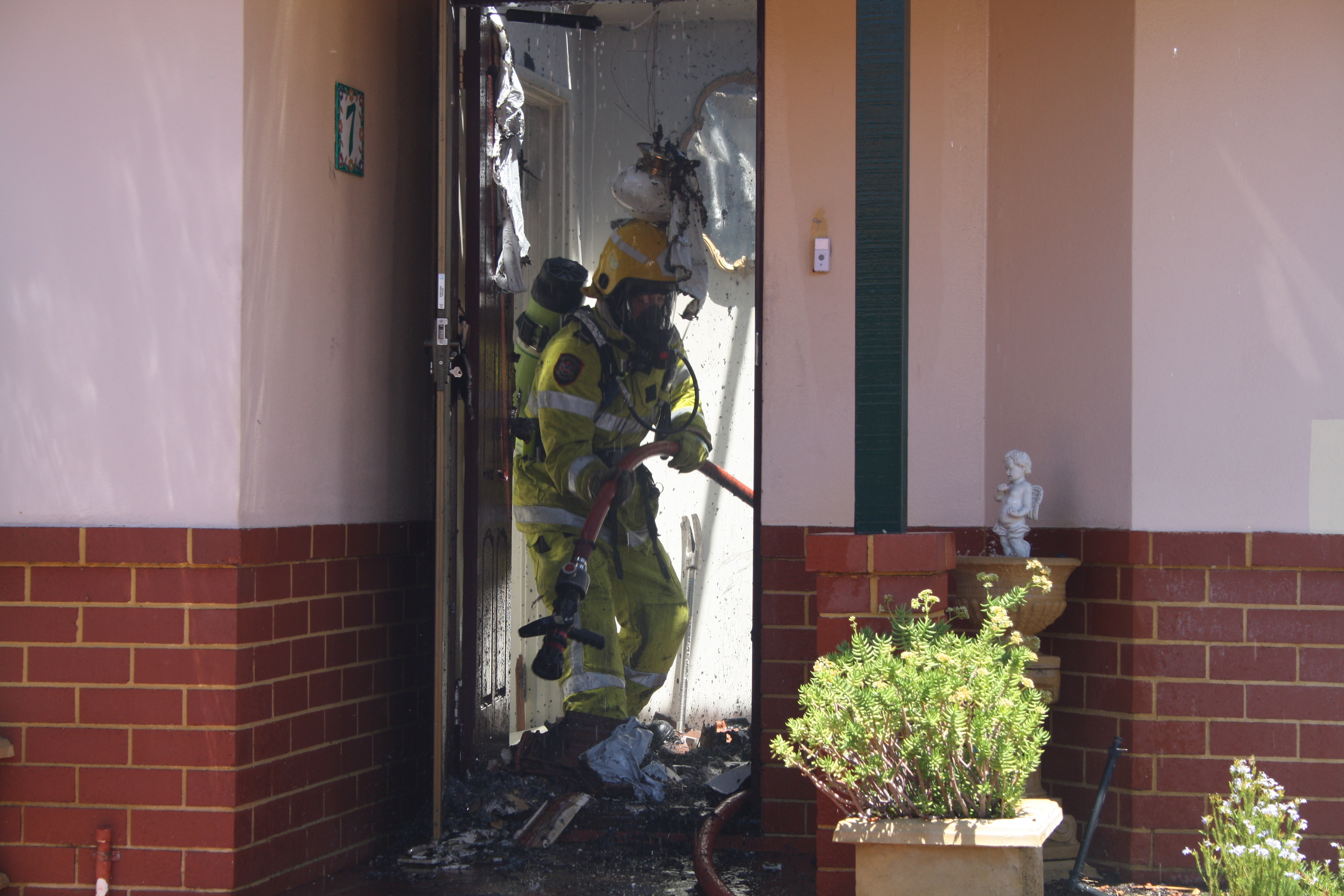 A fire fighter douses the house. Photo: Giovanni Torre