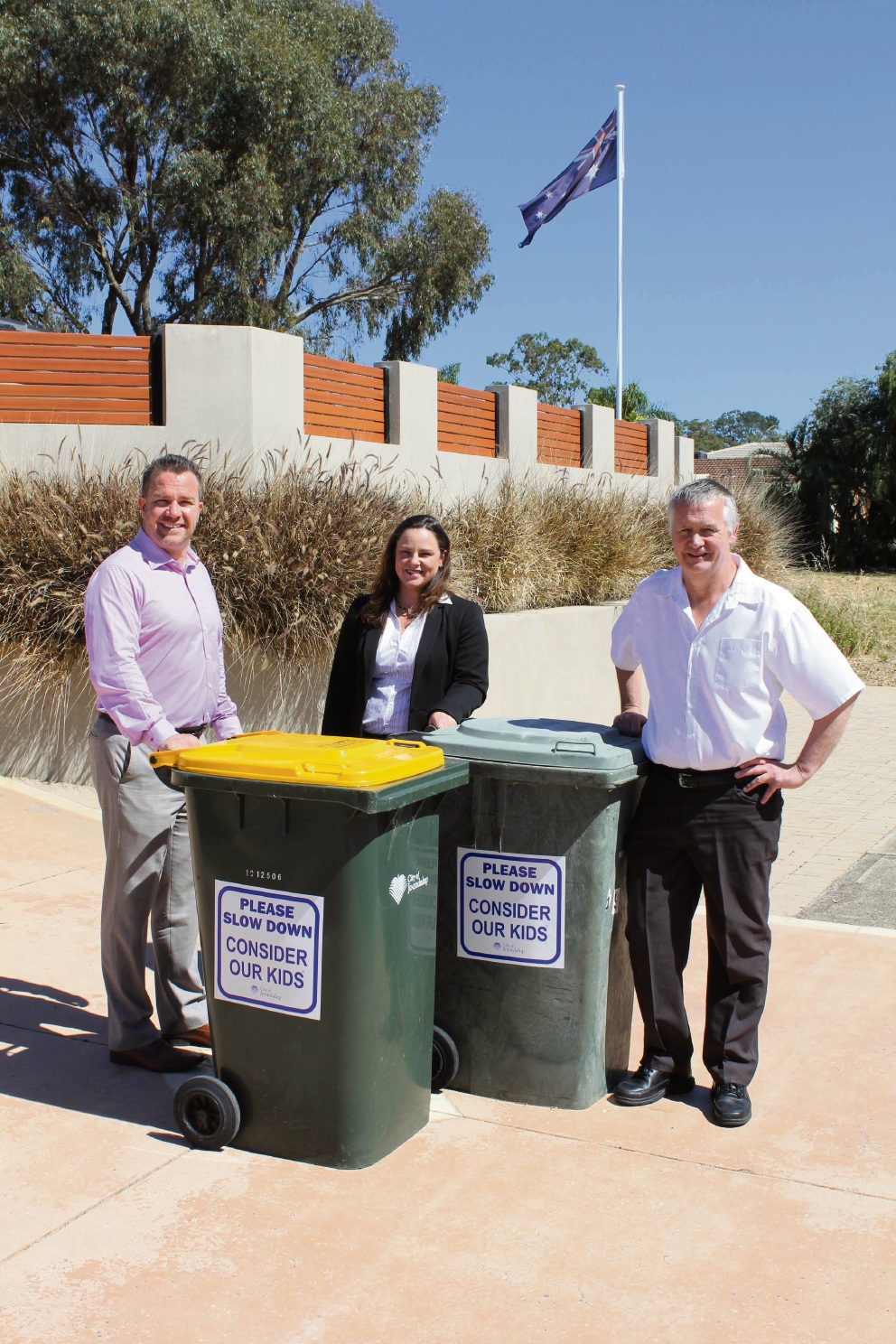 Joondalup Mayor Troy Pickard, Kingsley resident Jo-Dee Mansell and Cr John Logan with Ms Mansell's bins sporting the new stickers.