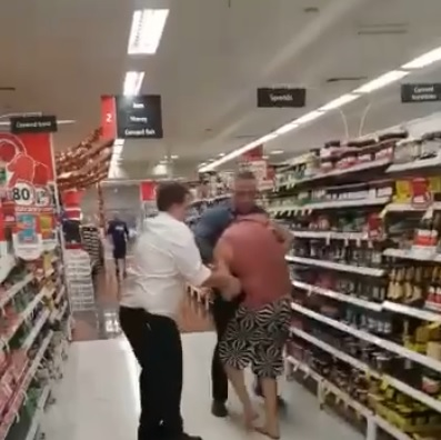 A still from the video showing a member of staff grabbing the shopper.