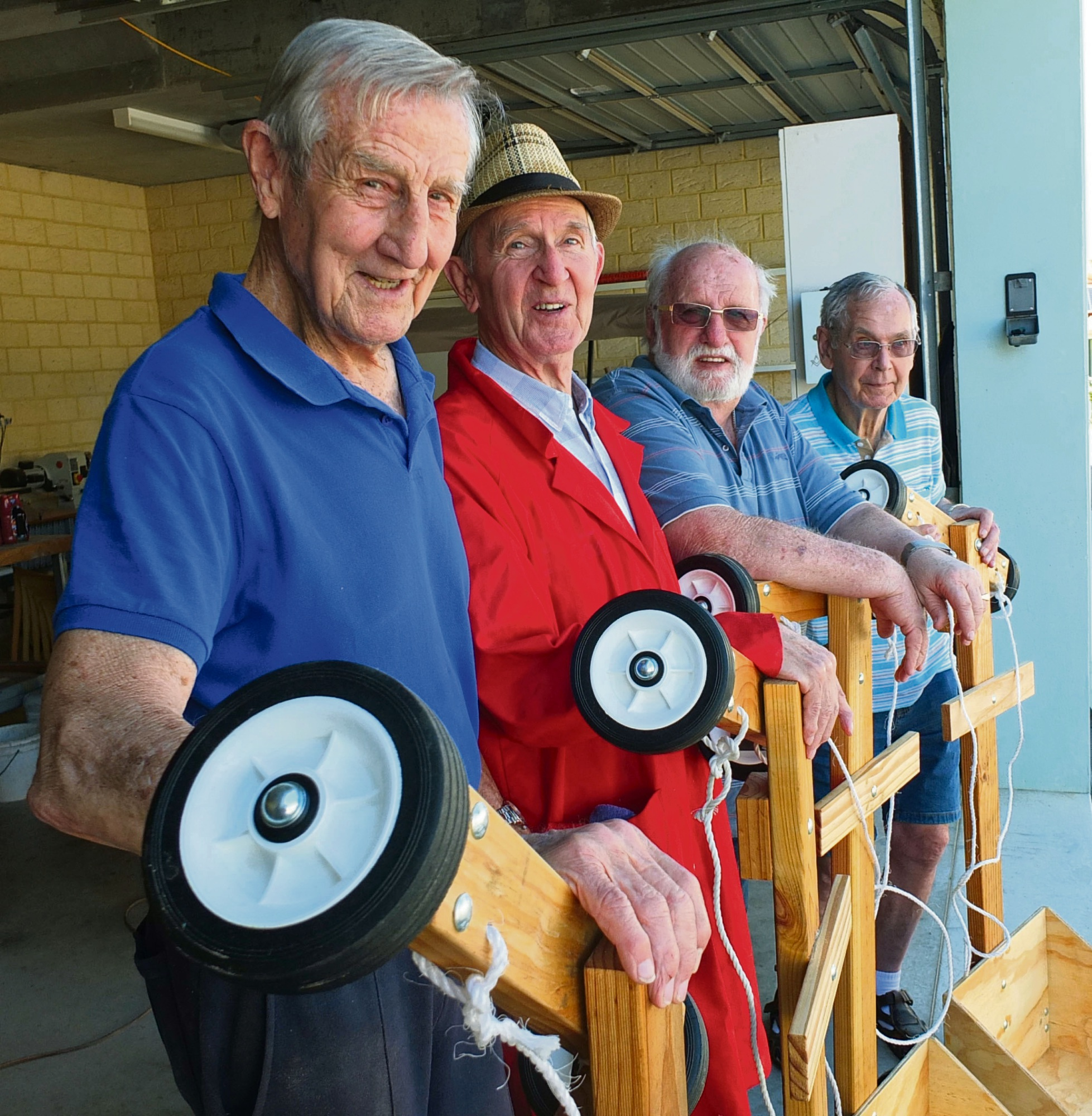 Regents Garden Men 's Shed members Buzza, Michael, Marinus and Abehard with the billy carts they made for this year's Show.