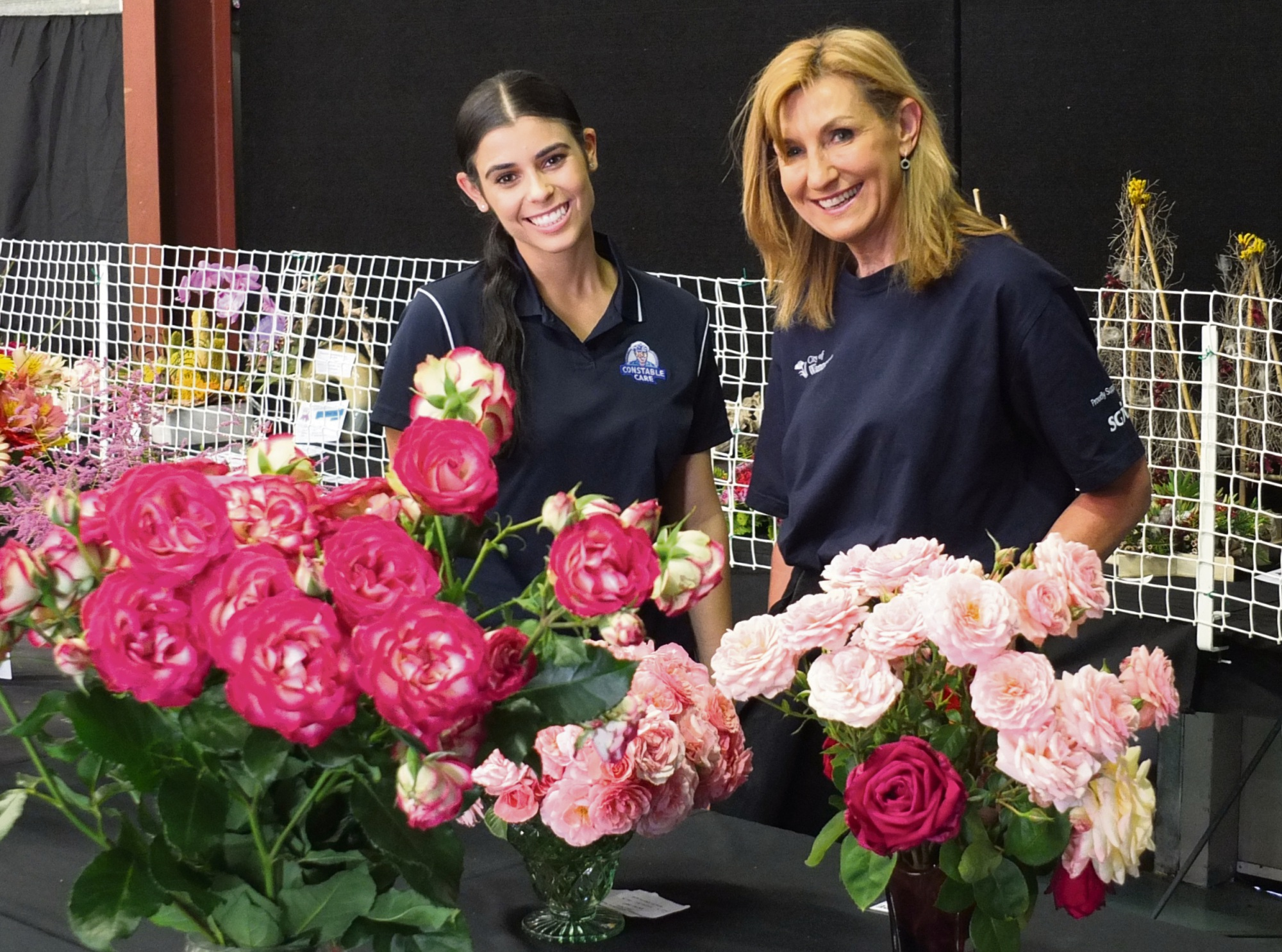 Crystal Della Post and Resmie Greer admire floral entries in the pavilion.