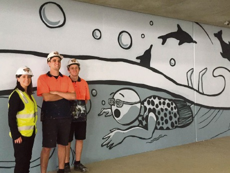 Centre manager Jacqueline McKenzie, Sam Shields and Elliott Tawns with a section of their underground carpark mural.