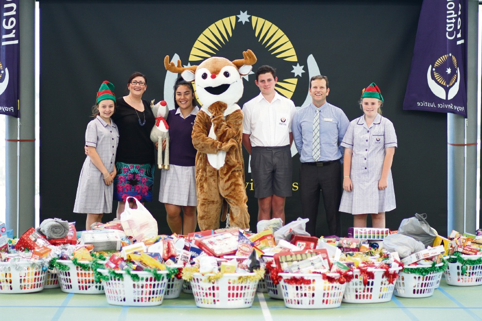 Lilly Varley, Cherie Milne, Ella Siakia, Nathan Clayton, John Swindells and Emma Wilson pose with the reindeer, Christmas hampers and other goodies.