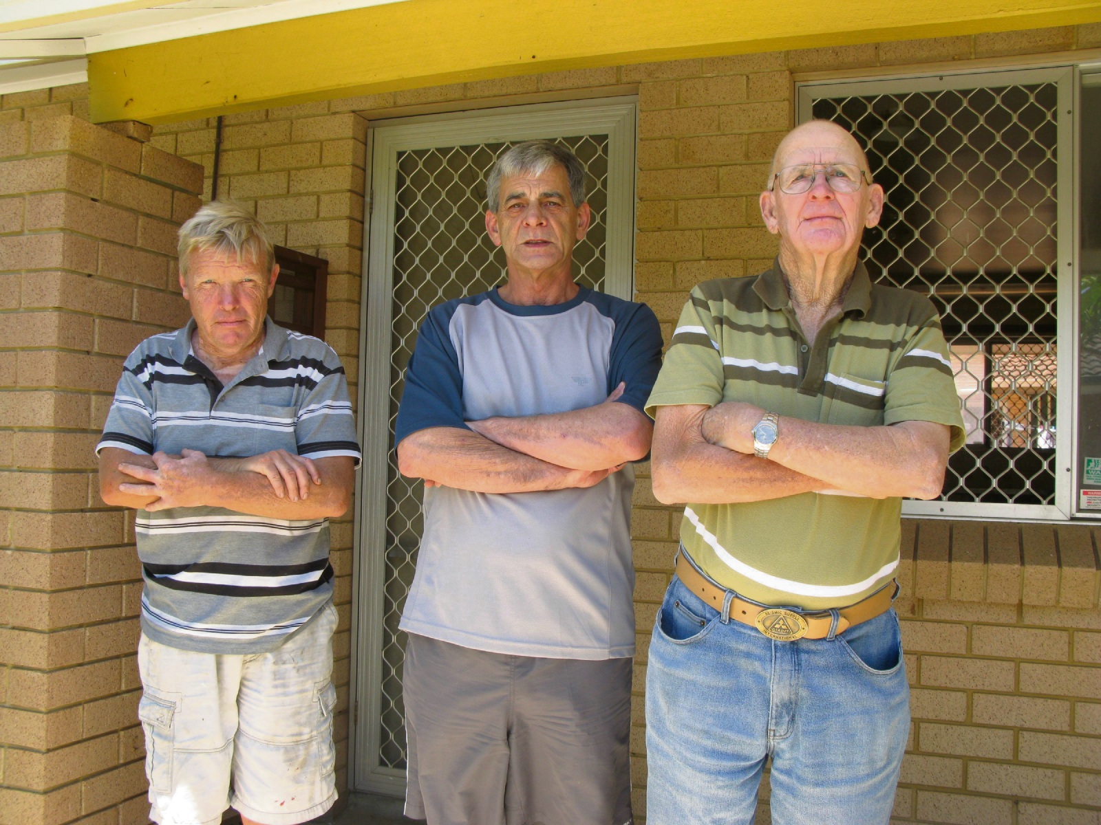Dudley Park residents Norman Bell, John Jansen and Keith Shaw outside the vacant unit they claim is a source of a disgusting smell and their vermin problem.