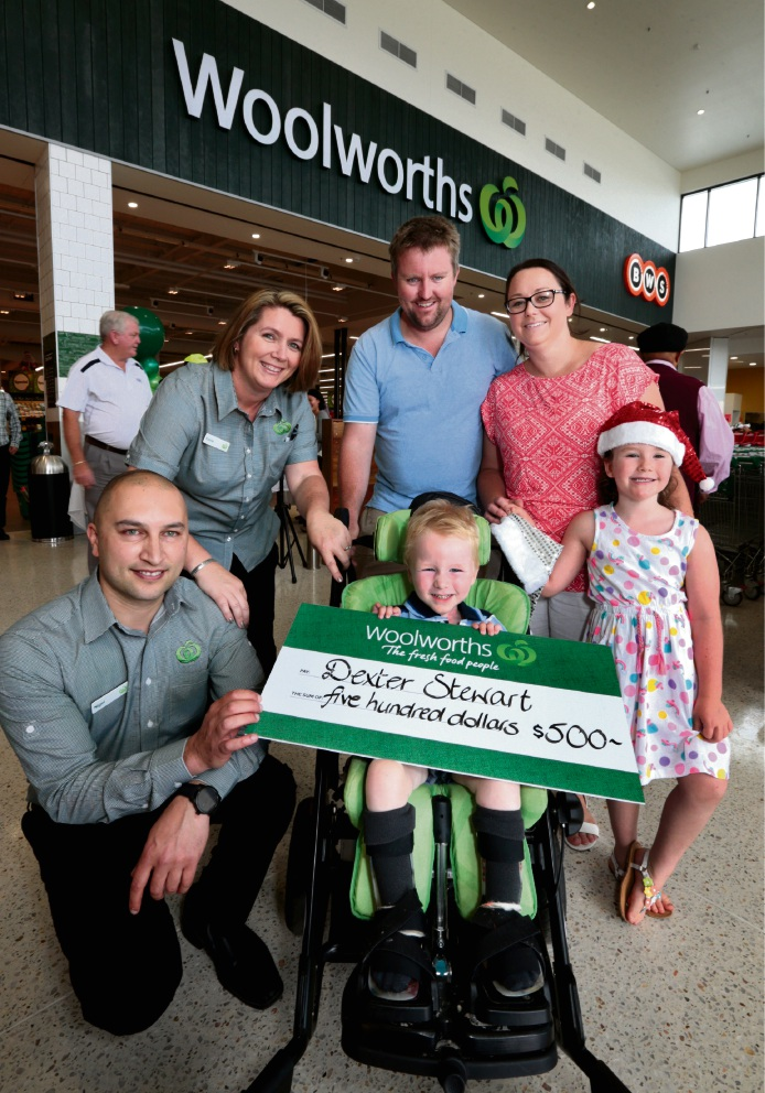 Store manager Nigel Jansze with staff member Kerrie Wysocki, Adam and Donna Stewart, Addison and Dexter at the shopping centre.  Pictures: David Baylis         d463130 The Aveley Primary School choir singing at the opening of Woolworths in the new Aveley Shopping Centre.
