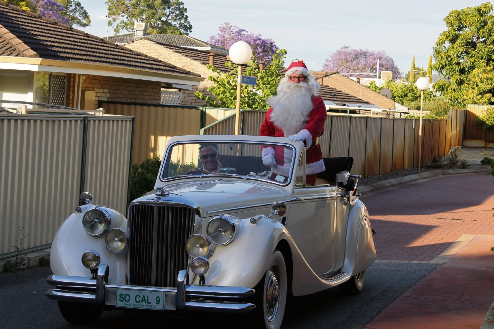 Santa arriving in a 1951 convertible Jaguar.