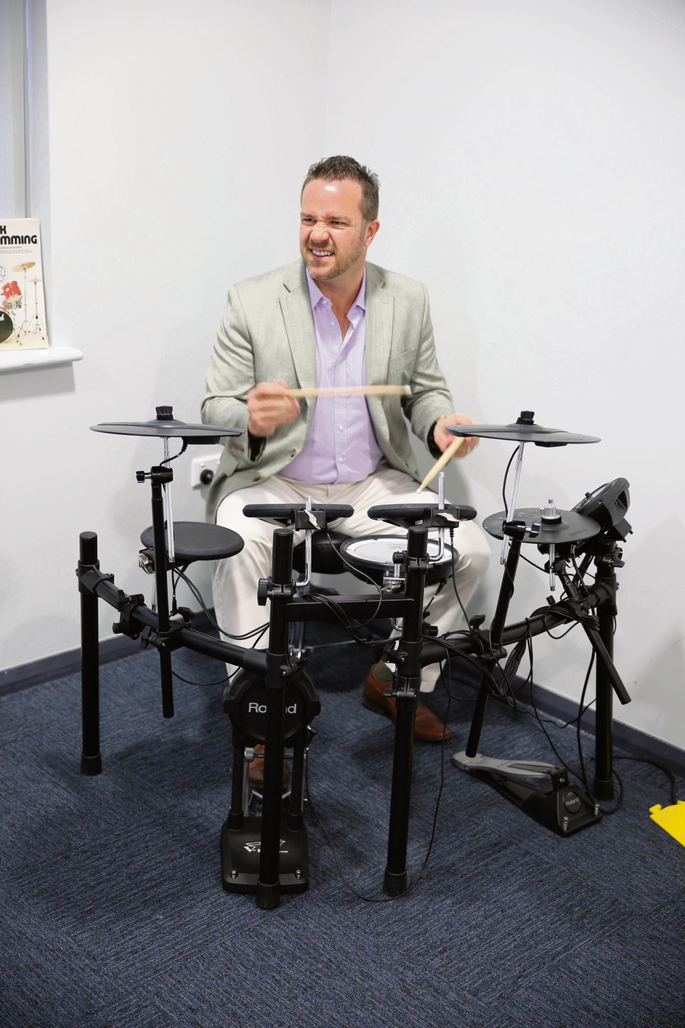 Mayor Troy Pickard tries out the drums at the Edge Youth Centre's music recording studio.
