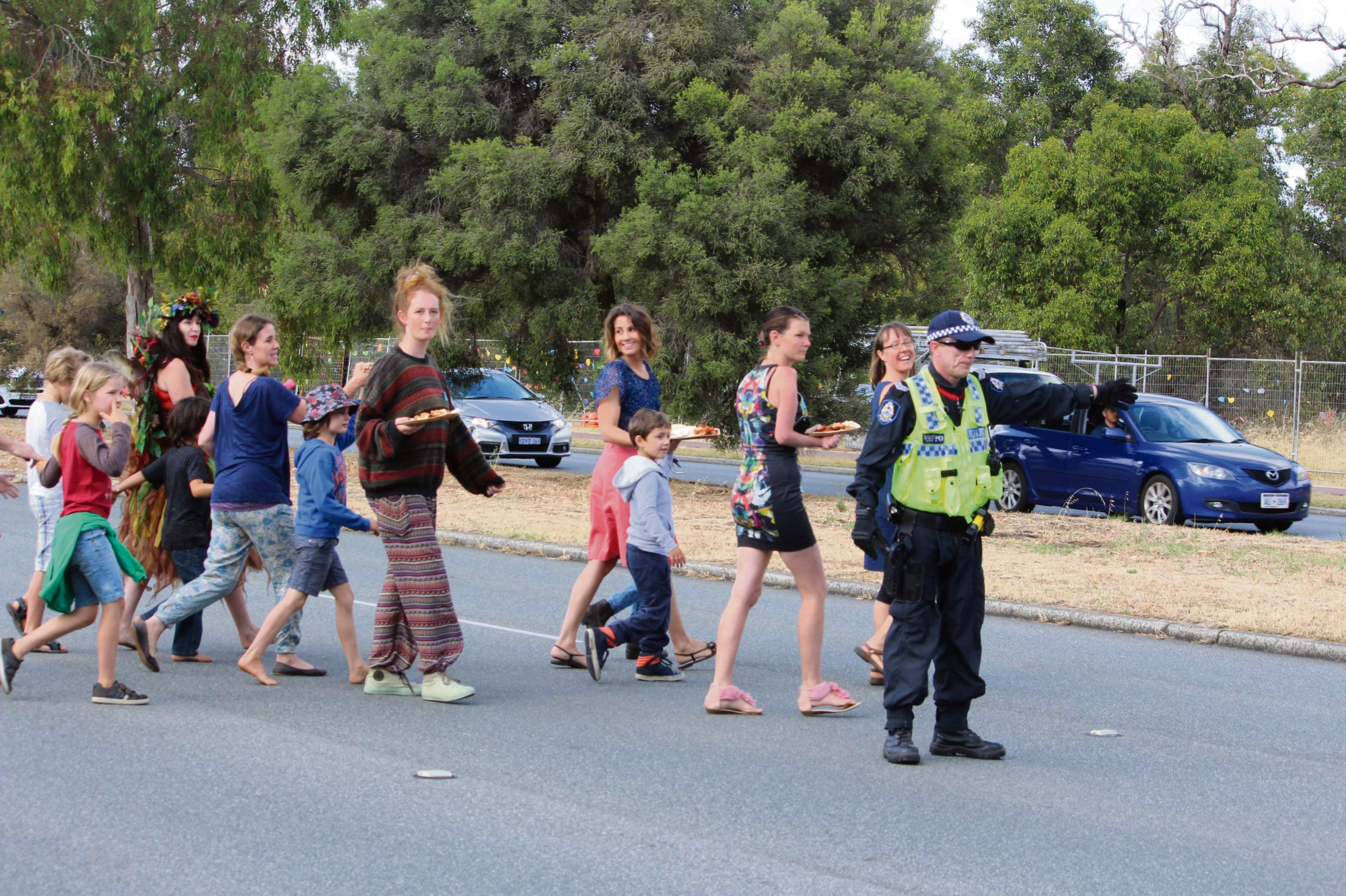 A police officer helps kids cross a busy North Lake Road this morning. Photo: Bryce Luff