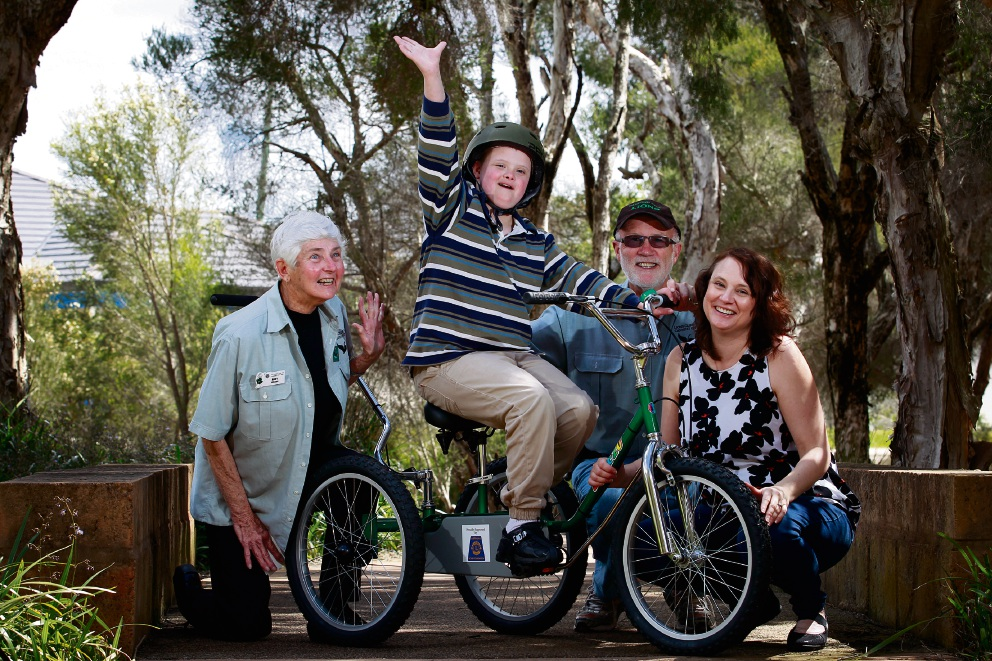 Mary Gregory and John Tidey from Canning City Lions Club with Matthew Guppy (10) on his new tricycle and his mother Corinne Guppy. Picture: Marie Nirme