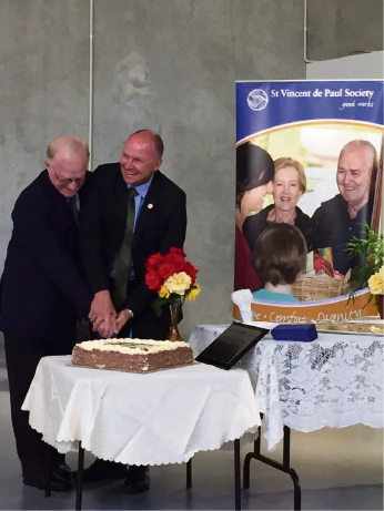 St Vincent de Paul chief executive Mark Fitzpatrick and Parliamentary Secretary Colin Holt cut the cake.