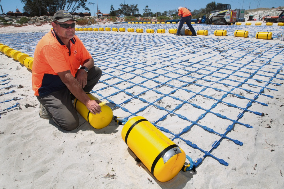 Eco Shark Barrier owner Craig Moss assembling the barrier. Picture: Bruce Hunt