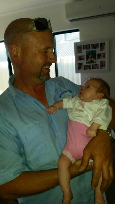 Mindarie Air and Electrical Services owner Kevin Hinds holding Phoebe Jury.