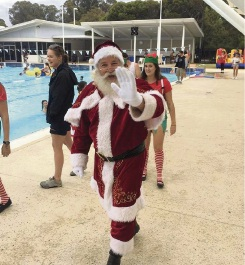Santa arrives at the Christmas Pool Party.