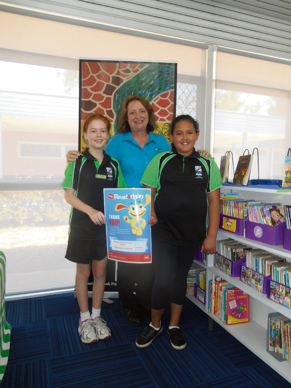 Readers for MS... Neerigen Brook Primary School students Ashley Dalton and Shevon McCormack with library officer Deborah Fearns.