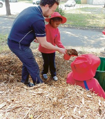 East Victoria Park Education Support Centre Student Selma Elrashid learns about mulch from student teacher David Bell.