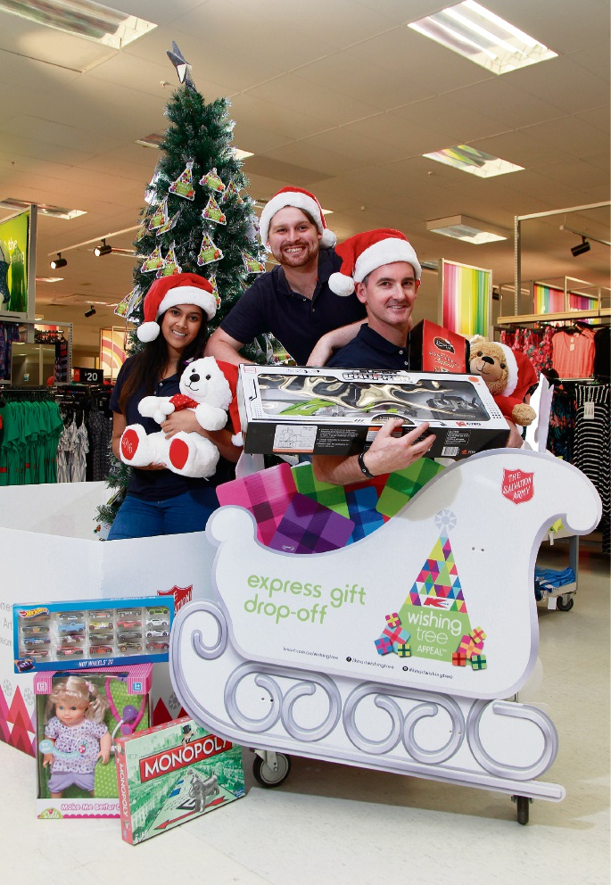 Kmart Belmont store manager Will Gould (in trolley) with store operator Savannah Machado and manager in training Max Browne-Cooper underneath the Wishing Tree. Picture: Marie Nirme