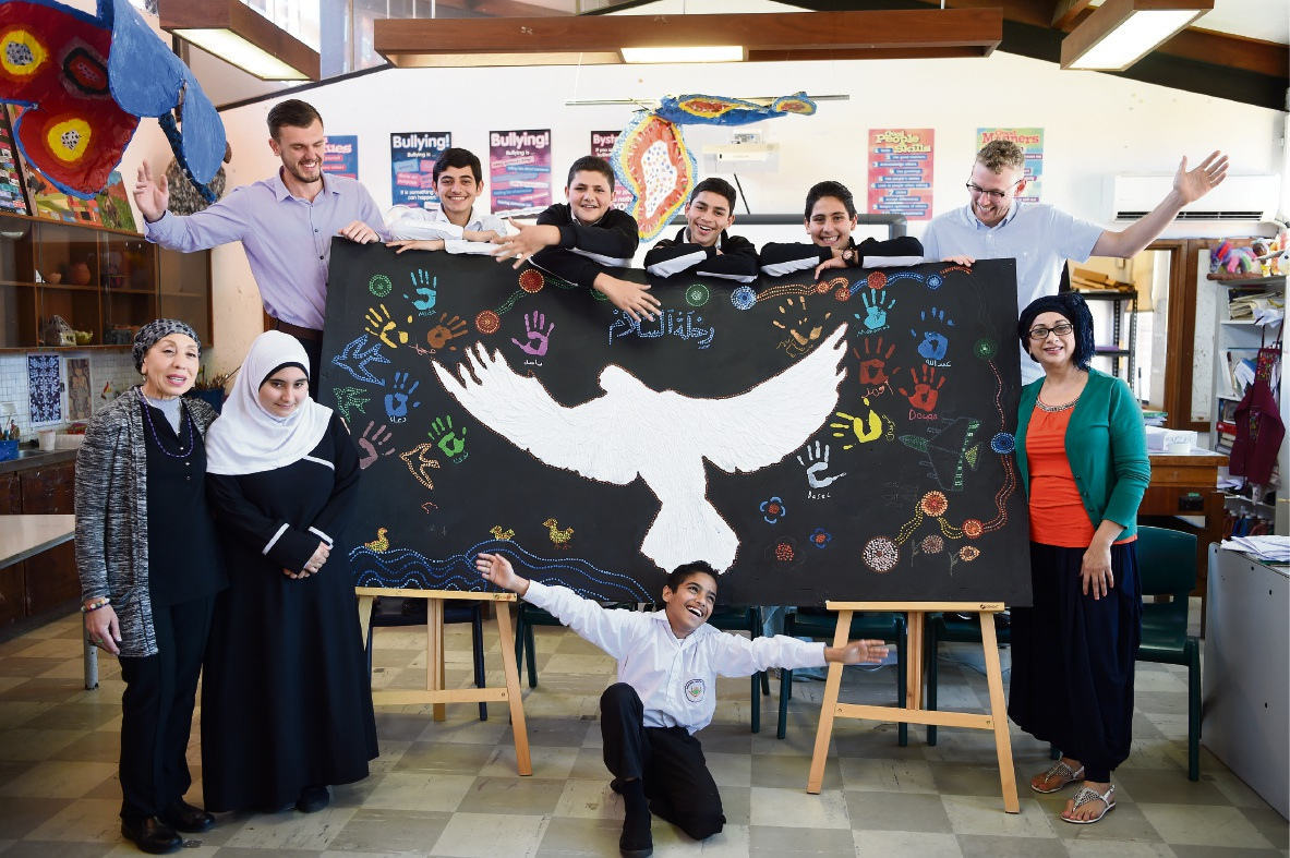Teachers James Atkins and Sam Cavallaro (standing, back) with art teachers Tina Mastrantonio, Amelia Joseph and Mohamed Moha (front) and some students. Picture: Jon Hewson