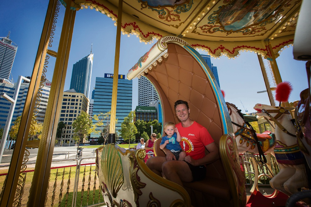 Elizabeth Quay visitor Mark Grogan with his son Huxley on the Venetian carousel. Picture: Will Russell          d463672
