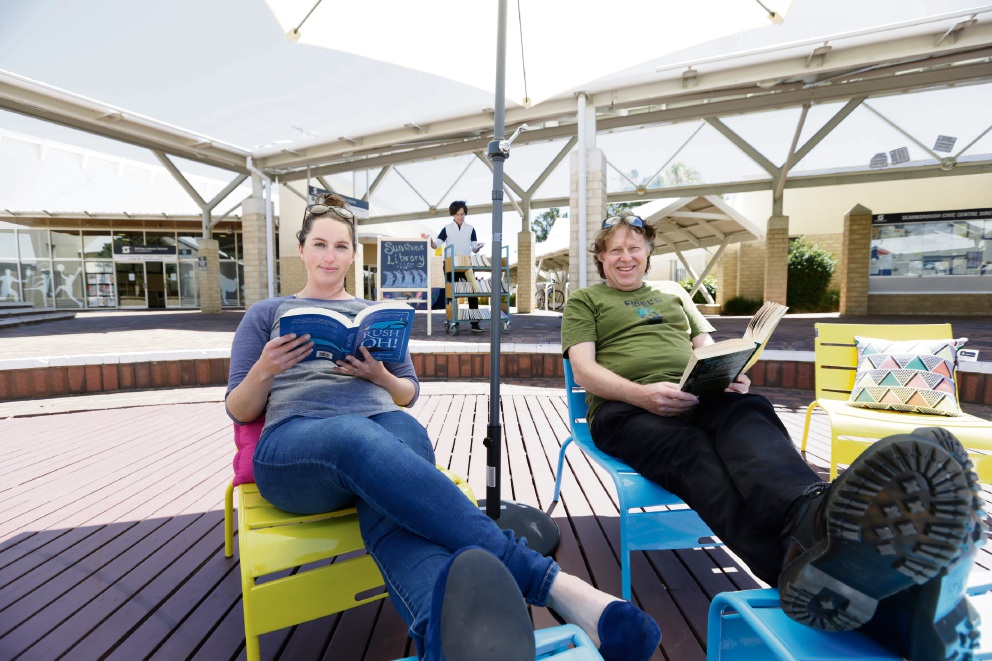 Suzy Eltoft and Steve Hellwig, with Sibylle Teichmann in the background, relax in the |outdoor reading area at Scarborough library. Picture: Andrew Ritchie        d464112