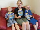 Stacey Harrison with daughters Charlotte and Emma Ward and Dolphin Buddy's Outdoor Adventure Journal.