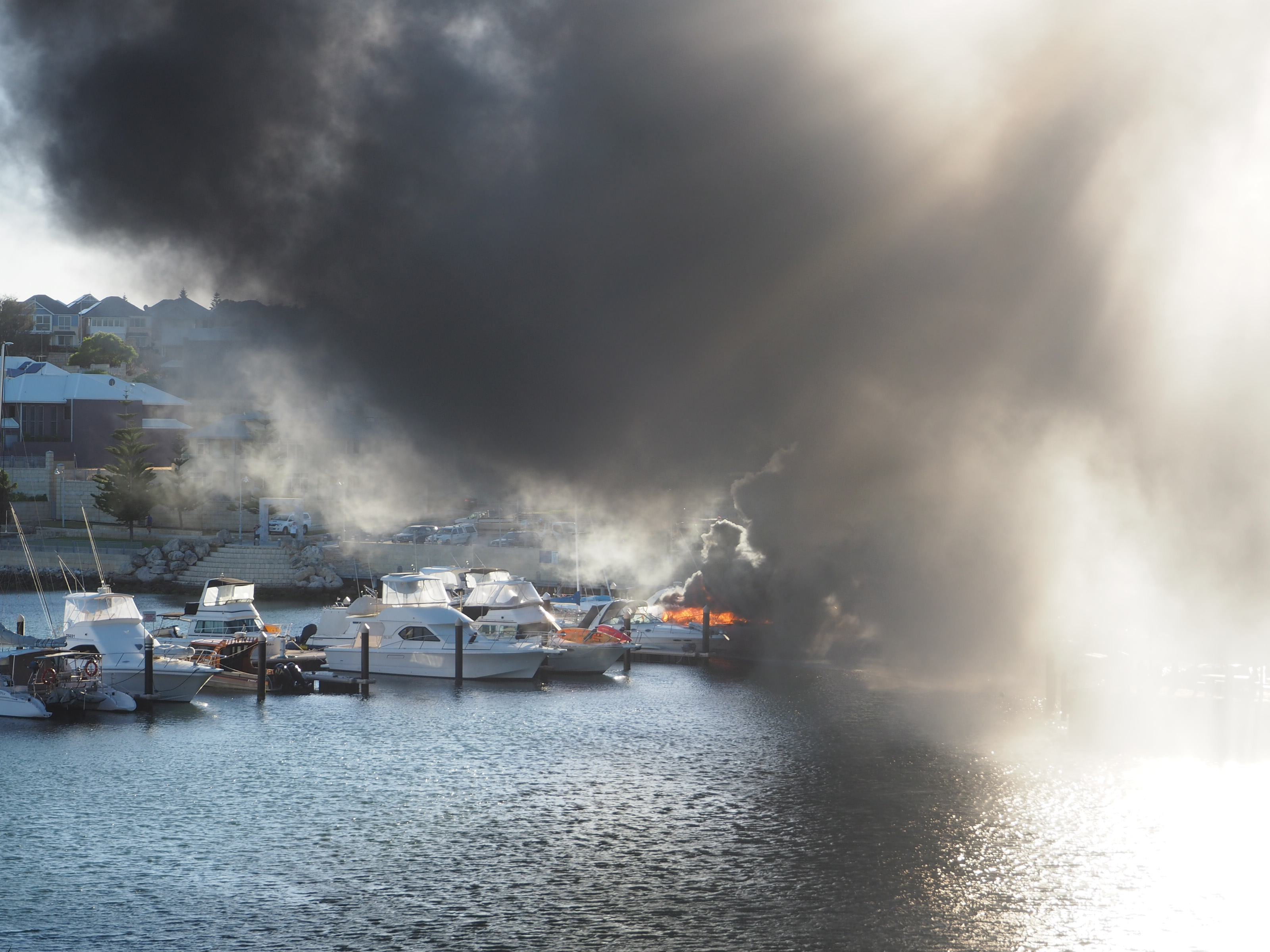 The vessel ablaze at Mindarie Marina. Pictures: Ian Goodenough.