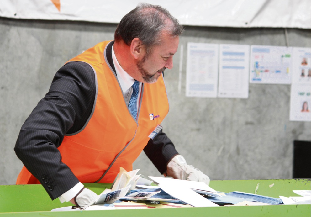 Commerce Minister Michael Mischin helps unload some of the 70,000 intercepted scam letters onto a CTI Logistics conveyer belt to be shredded.