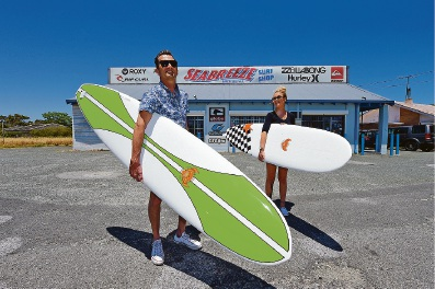 John and Sasha Hawkins at the front of Seabreeze Surf Shop, the business John started 30 years ago.