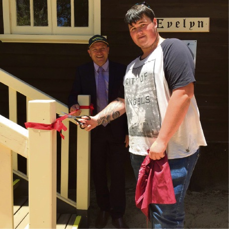 Fairbridge apprentice Brent Appleton cuts the ribbon watched by Colin Holt MLA who officially opened the cottage.