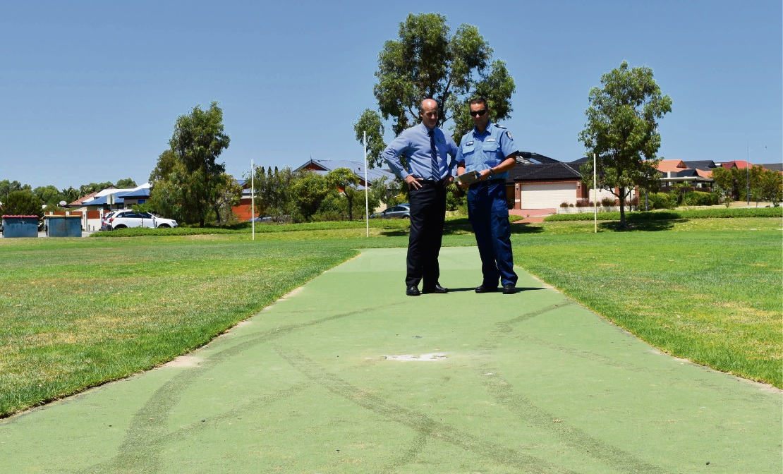 Comet Bay PS principal Graeme Watson and Sgt Paul Trimble examine the damaged cricket pitch.